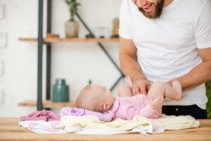 Young father play with laying baby girl. Child is lying on table, dad smiles.