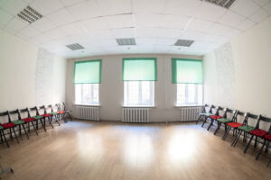Large hall with three windows interior. Chairs along two sides, hardwood floor, beige walls and green curtains.